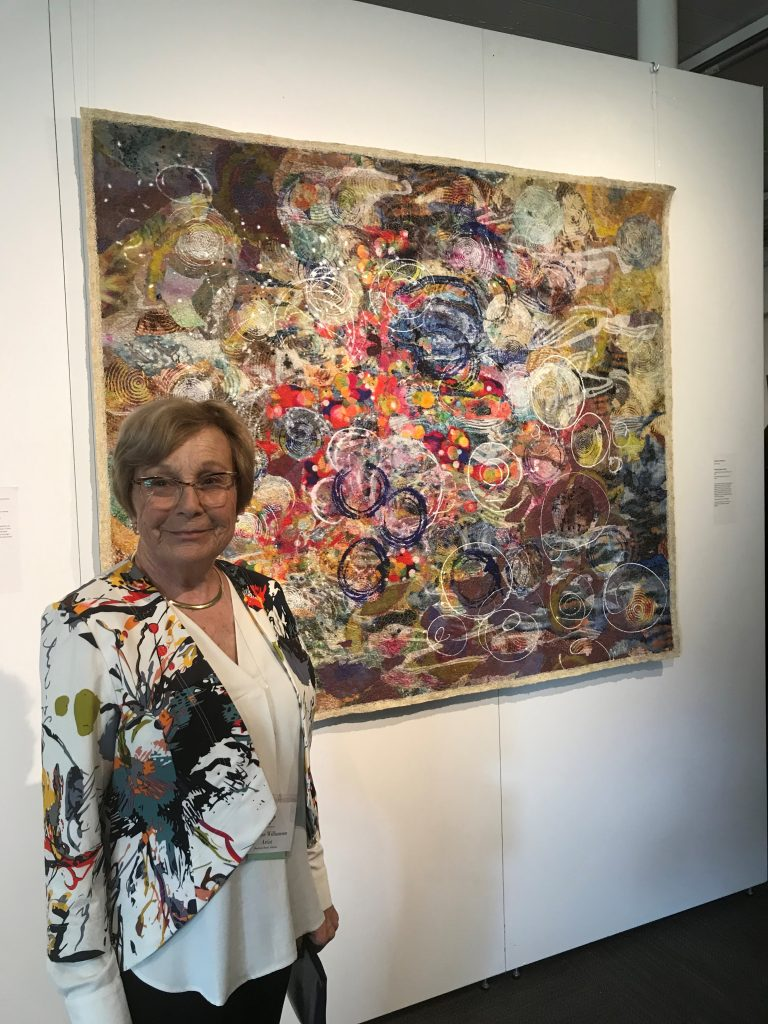 Marianne Williamson standing next to her Prayers Going To Heaven painting featured at the opening of Quilt National 2019 in Athens Ohio
